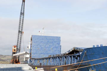 large ship being loaded with steel
