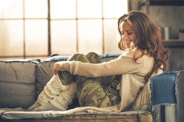 Relaxed young woman sitting in loft apartment