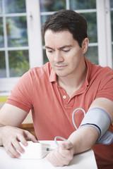 Man Measuring Blood Pressure At Home