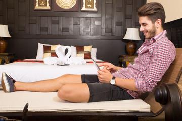 Junger Mann mit Tablet Pc im Hotelbett