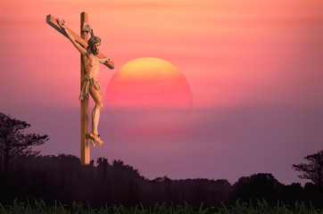 Jesus and the cross over blurred sunset