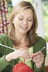 Woman Enjoying Knitting Garment At Home