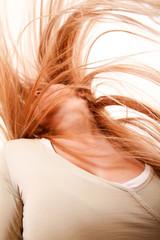 Blondes Mädchen schüttelt ihr Haar