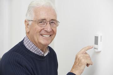 Smiling Senior Man Adjusting Central Heating Thermostat