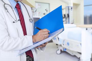 Doctor writing on a folder