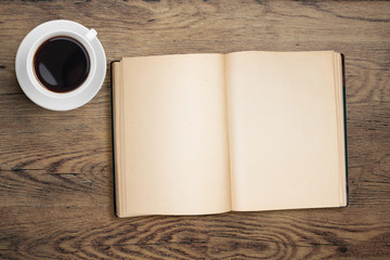 open book and coffee cup top view on table