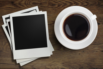 coffee cup and polaroid photo frames on wooden table top view