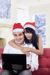 Happy couple using laptop for buy online