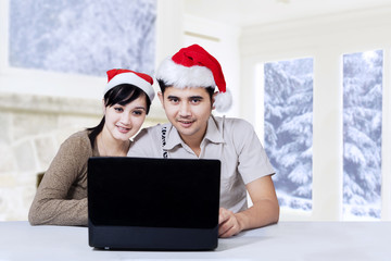 Happy couple using laptop in christmas day