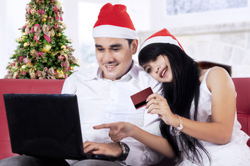 Hispanic couple shopping online in christmas day