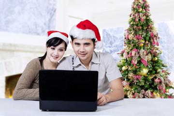 Hispanic people with laptop enjoy christmas day