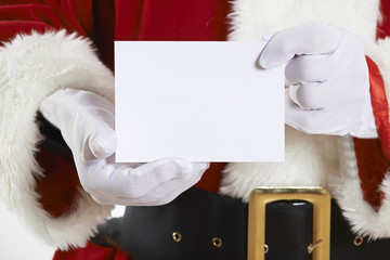 Close Up Of Santa Claus Holding Blank Invitation