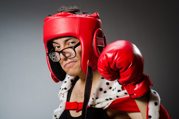 Funny boxer with red gloves against dark background