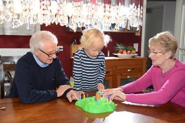 Großeltern spielen mit Enkelkind ein Gesellschaftsspiel