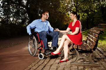 Disable man on wheel chair - happy with girl