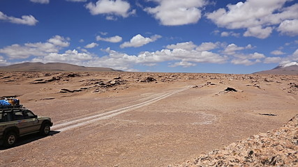 Car driving through the desert in the Altiplano, Bolivia