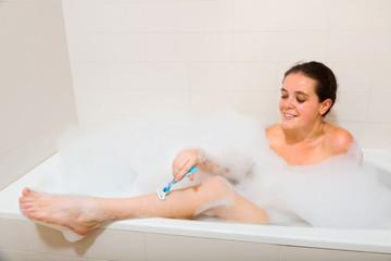 Woman shaving legs in bath