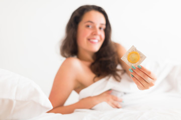 Girl with condom in bed
