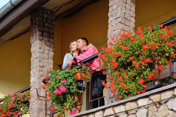 Man and woman together on balcony of their house or hotel with b