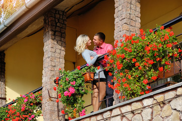 loving couple on a balcony with flowers