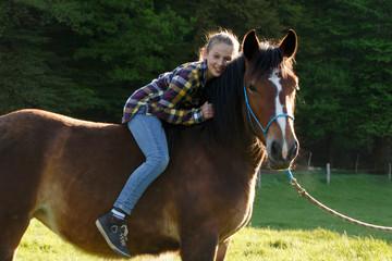 Jugendliche fröhlich auf dem Pferd