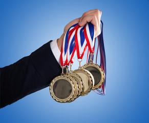 Businessman's Hand Holding Medals Over Blue Background