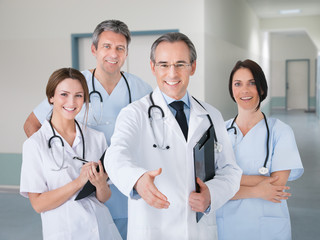 Doctor Offering Handshake While Standing With Team In Hospital