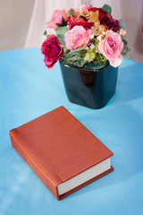 Beautiful bouquet of rose flower in vase with old notebook