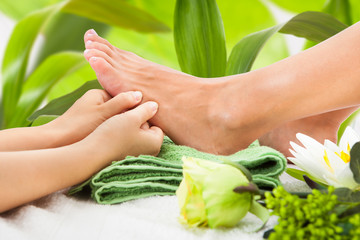 Masseuse Massaging Woman's Foot Against Leaves