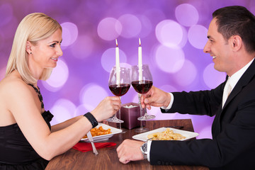 Romantic Couple Toasting Wineglasses In Restaurant