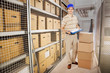 Delivery Man Holding Clipboard By Cardboard Boxes In Warehouse