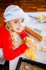 Mädchen backt in der Küche Weihnachtsplättchen