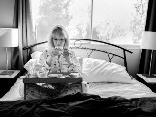 Mature Woman Having Breakfast in Bed