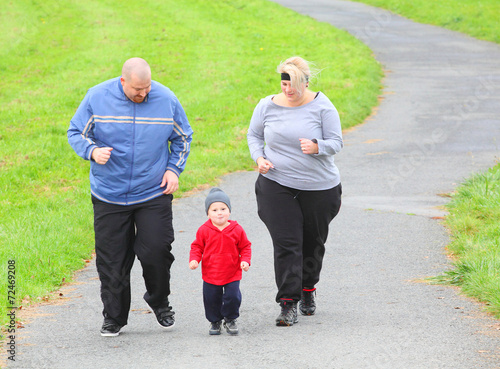 Leinwandbild Motiv Overweight parents with her son running together.