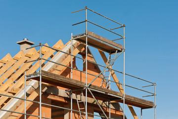 Ein Baugerüst am Giebel von einem Neubau unter blauem Himmel