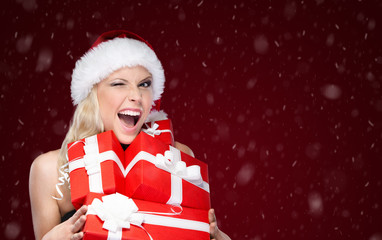 Pretty woman in Christmas cap holds a set of presents