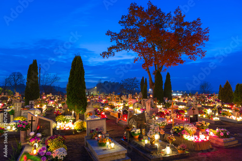Fototapeta Cemetary at night with colorful candles in All Saints Day