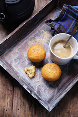 cupcake with cup of coffee on old wooden tray with cast iron pot