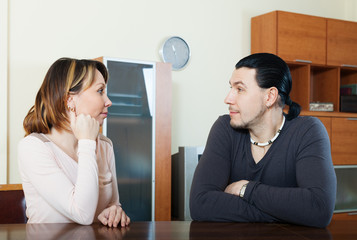Serious couple talking in home