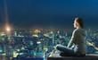 Leinwandbild Motiv Woman is sitting over the city