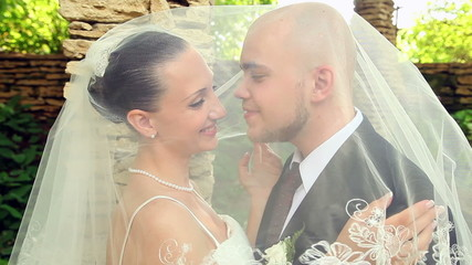 groom kisses the bride under a veil
