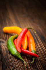 spicy chili peppers on a wooden background