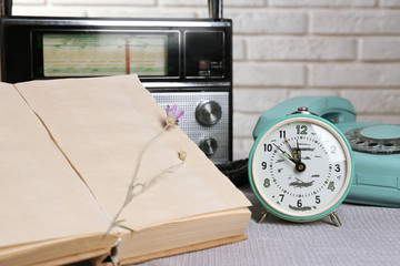 Retro composition with old phone, radio, clock and books, close