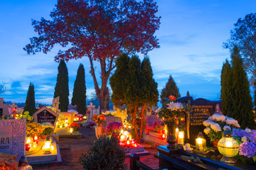 Cemetery at night with colorful candles in All Saints Day