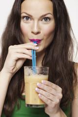 Portrait of a Woman Drinking Yellow Fruit Juice