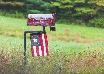 Roadside Mailbox with Antique Flag found in Country setting.