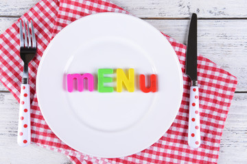 Inscription menu on plate on table close-up