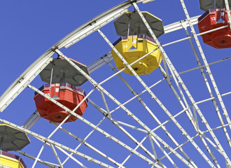 Colorful Ferris Wheel in amusement park with blue sky