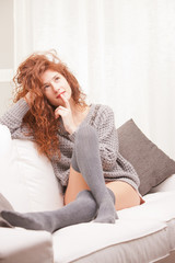 Red Headed  girl thinking on her sofa