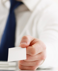 Portrait of young handsome business man holding blank white
